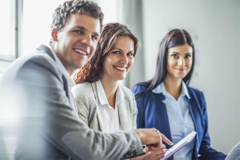 Hier würden Sie drei Mitarbeiter sehen, die sich über Geschäftsreisen unterhalten.